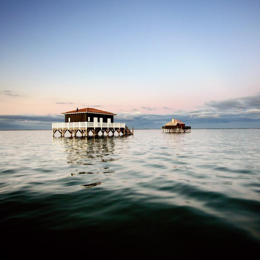 Photos du Bassin d'Arcachon : les cabanes tchanquees à marée haute pendant l'été indien après le coucher du soleil