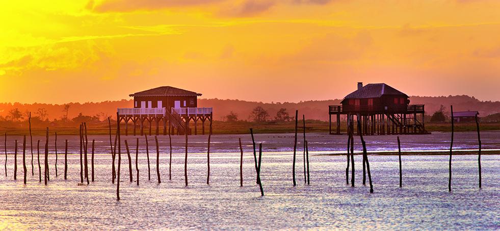 Photo du Bassin d'Arcachon : les emblématiques cabanes tchanquees de l'ile aux oiseaux au coucher du soleil. Photo de Stéphane Scotto